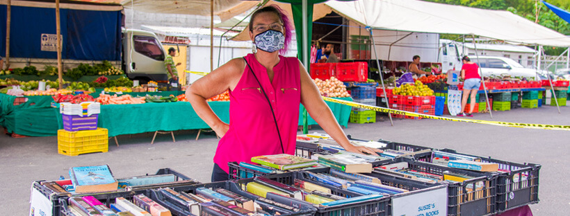 Woman wearing a mask in bright pink shirt with matching hair standing behind a table full of used books at a farmers market.