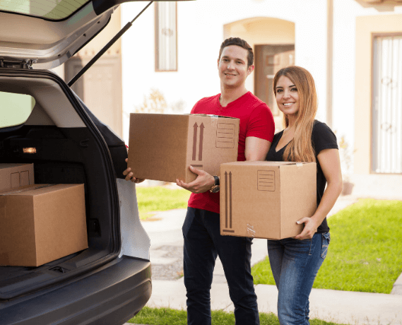 male and female smiling loading boxes into back of car