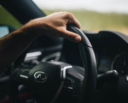 A driver's hand on a car steering wheel