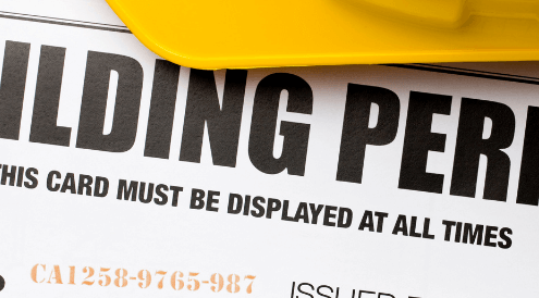 Stack of blueprints with Building Permit text across the top with yellow hard hat