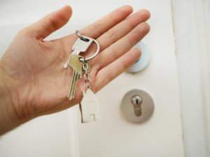 A close up photo of a hand holding keys in front of the home door