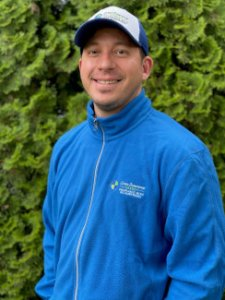 Profile image of Elliot Cox in blue Cross Insurance Agency fleece and truckers hat standing in front of large juniper hedge.